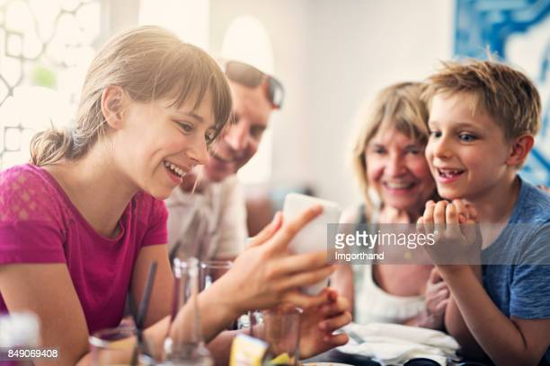 Little girl showing funny app to her family
