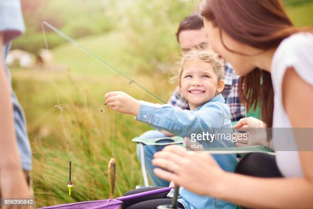 little girl showing mum the fish she's caught