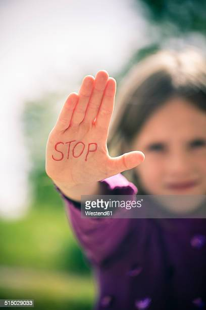 Little girl showing palm with the word STOP on it