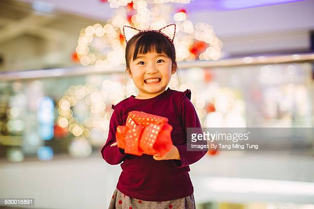 Little girl similing joyfully with a gift in mall