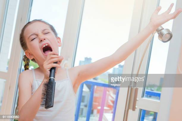 little girl sings and dabbles - girls open mouth stock photos and pictures