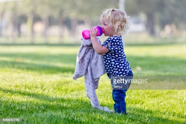 Little Girl Sips on Her Sippy Cup While Holding Her Blanket in a Park
