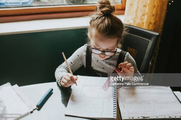 little girl sits at a kitchen table and does her homework / home schooling - homework stock pictures, royalty-free photos & images