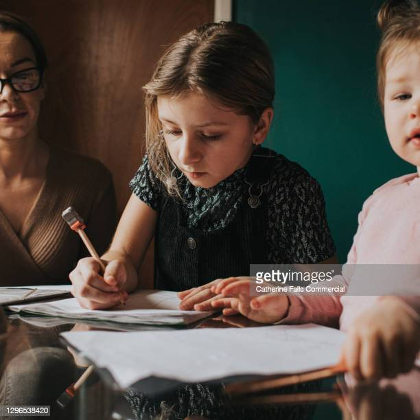 little girl sits at a kitchen table and does her homework / home schooling - inconvenience stock pictures, royalty-free photos & images