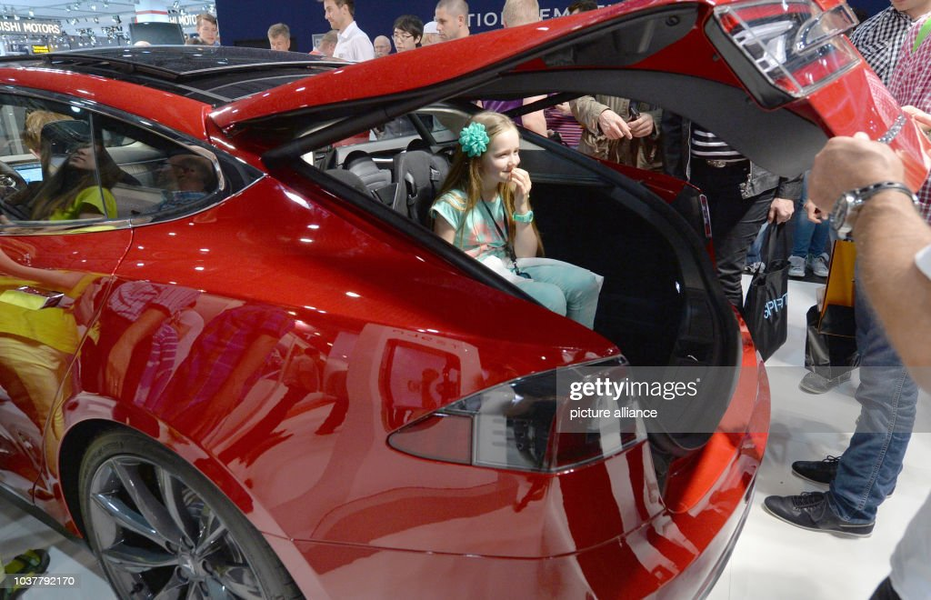 A little girl sits in the trunk of a Tesla S at the Auto Mobil