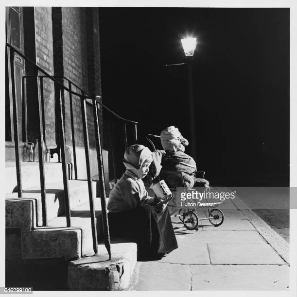 A little girl sits on a stairway collecting pennies for her guy as part of a Guy Fawkes Day tradition