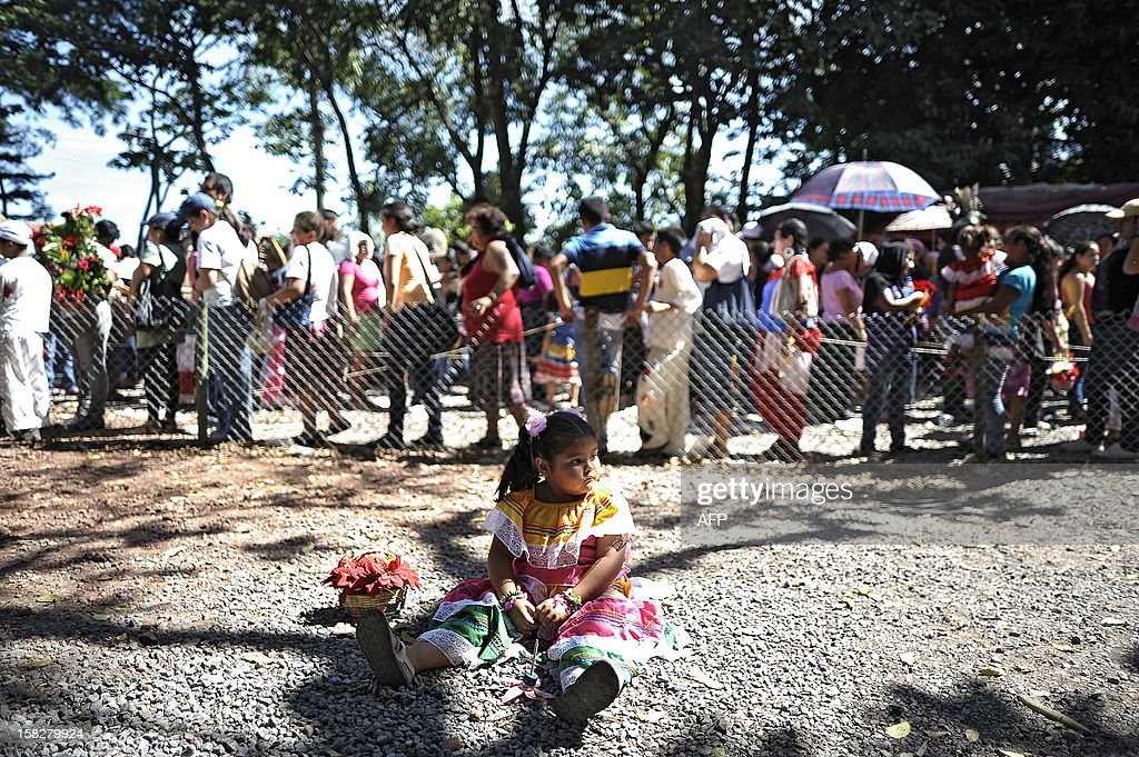 A little girl sits on the grounds as people queue to venerate the Virgin of Guadalupe at the Basilica de Guadalupe in San Salvador on December 12, 2012. Salvadorean faithfuls celebrated the appearance of the Virgin of Guadalupe to Juan Diego in 1531. AFP PHOTO/ Jose CABEZAS