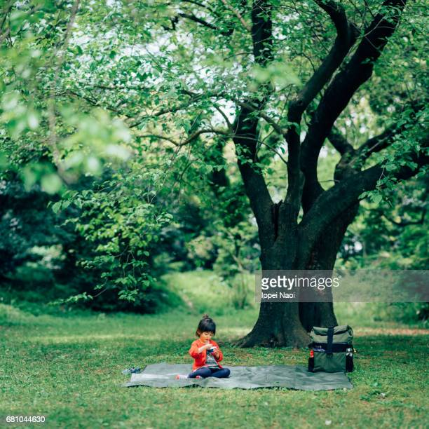 Little girl sitting and eating alone under tree in park