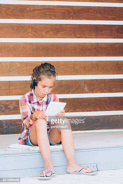 Little girl sitting and using digital tablet