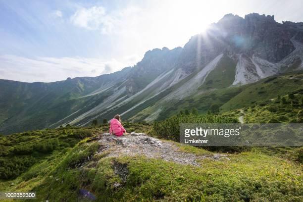 kleines Mädchen sitzt auf einem Berg