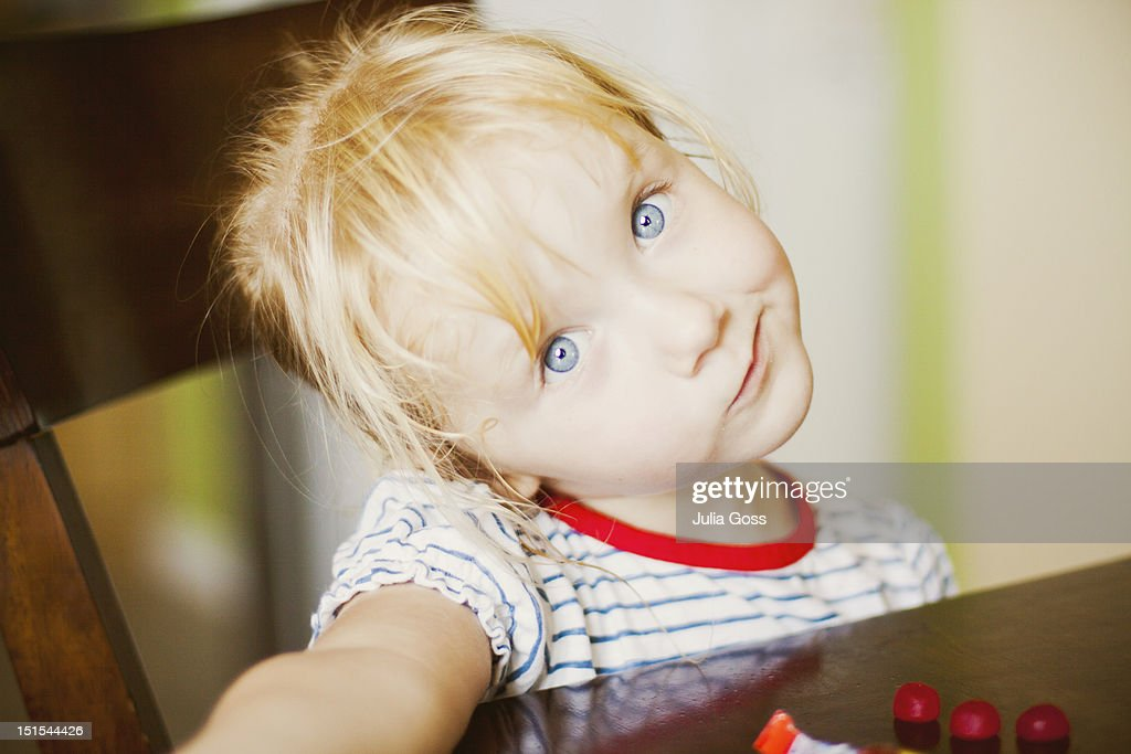 Little girl sitting at dining table : Stock Photo