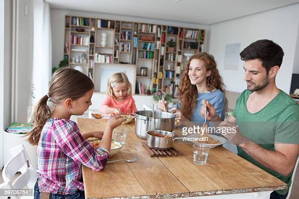 Little girl sitting at dining table with her parents and sister eating spaghetti