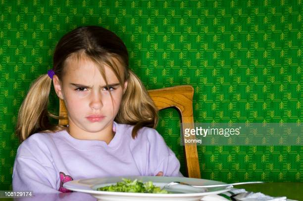 Little Girl Sitting at Dinner Table with Plate of Broccoli