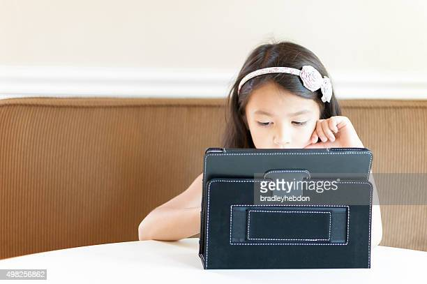 Little girl sitting at kitchen table with iPad