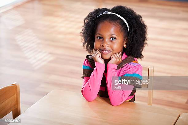 Little girl sitting at table in preschool classroom