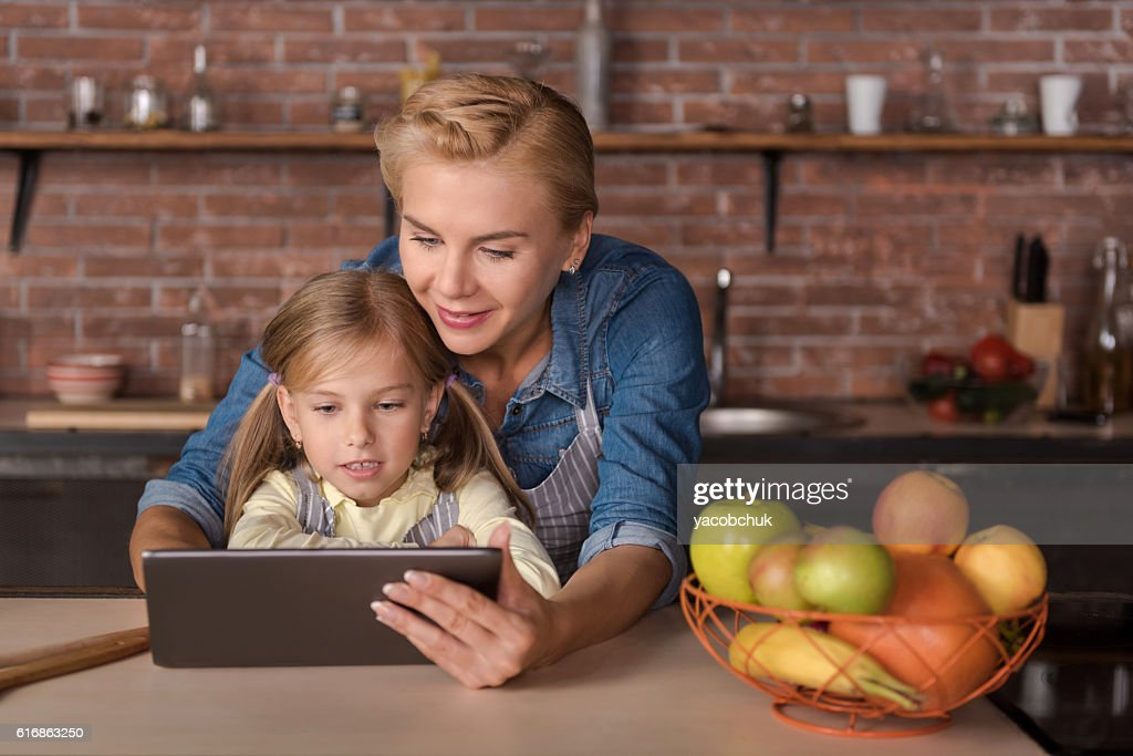 Little girl sitting at the table with her mother : Stock Photo