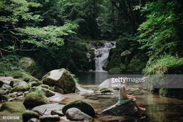 little girl sitting by a forest stream, japan - 茨城県 ストックフォトと画像