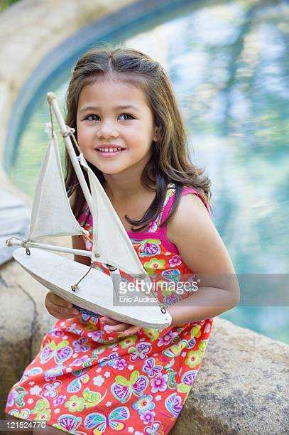 Little girl sitting by the swimming pool with model of boat in hand