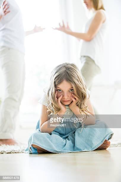 Little girl sitting cross-legged on floor, parents arguing in background