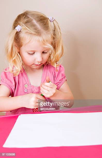 little girl sitting drawing pictures