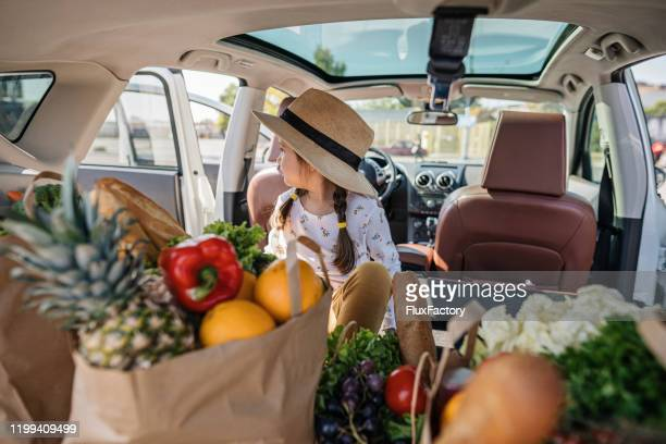little girl sitting in a car trunk surrounded with bags of groceries - boot stock pictures, royalty-free photos & images
