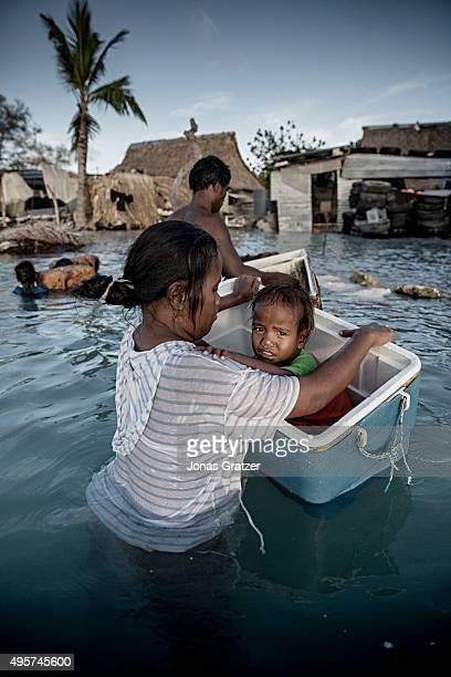 A little girl sitting in a floating cooler box after her village was flooded by the sea The people of Kiribati are under pressure to relocate due to...