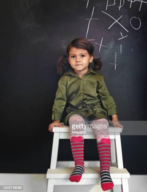 Little girl sitting in a front of a blackboard
