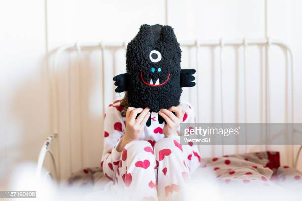 little girl sitting in bed hiding face behind her soft toy - monstruo fotografías e imágenes de stock