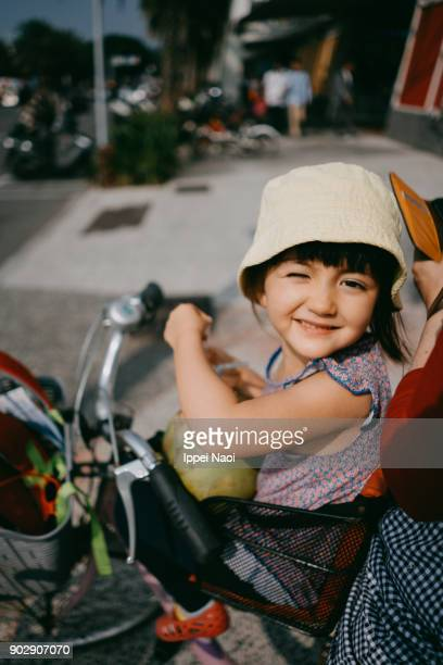 Little girl sitting in bicycle child seat, winking at camera