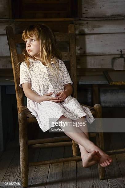 Kleines Mädchen sitzt auf einem Stuhl auf der Veranda