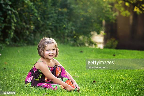 little girl sitting in grass in front of river - rebecca nelson stock pictures, royalty-free photos & images