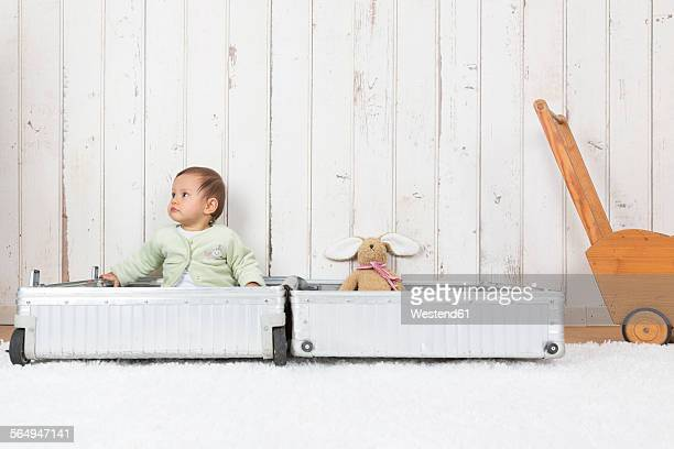 Little girl sitting in open suitcase with soft toy, looking away