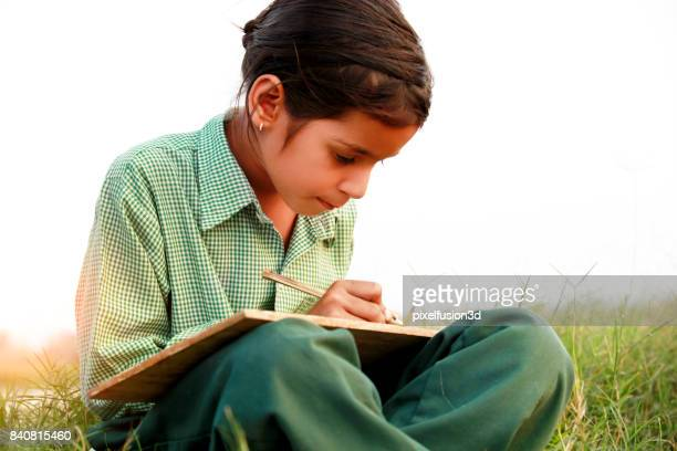 Little girl sitting in the field & writing portrait in the nature