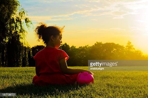 Little Girl (6-7) Sitting Next To Her Piggy Bank, Outdoor