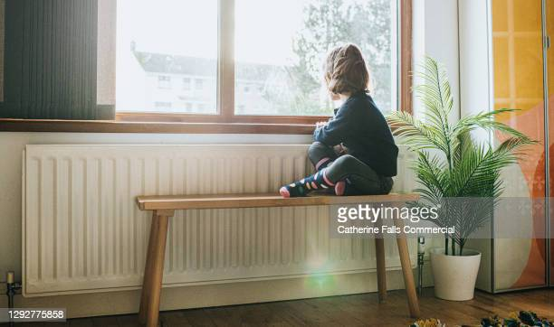 little girl sitting on a bench by a sunny window in a domestic room, looking out of the window - childhood stock pictures, royalty-free photos & images