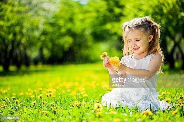 Little girl sitting on a fielf od fandelions