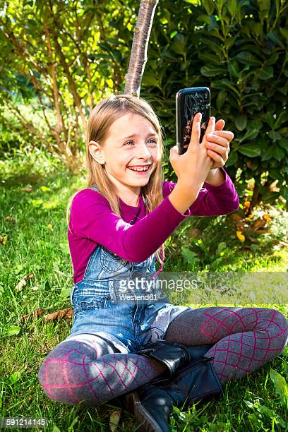 little girl sitting on a meadow in the garden taking a selfie with smartphone - little girls in tights stock photos and pictures