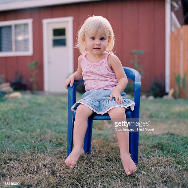 A little girl sitting on a plastic chair in a yard