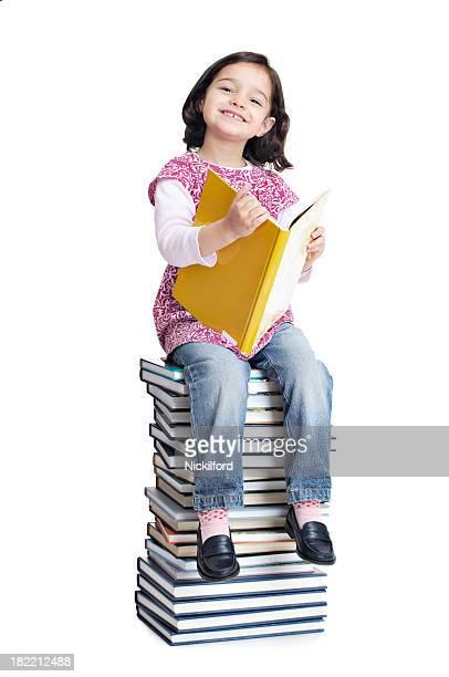 Uma menina sentada na pilha de Livros