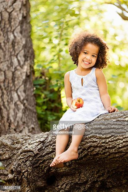 little girl sitting on a tree trunk with an apple - kid girl eating apple stock photos and pictures
