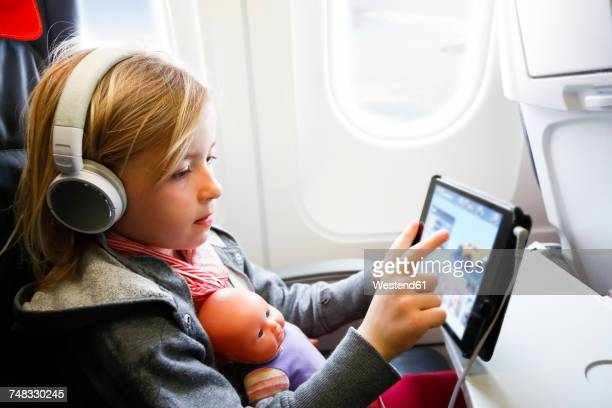 Little girl sitting on an airplane watching something on digital tablet