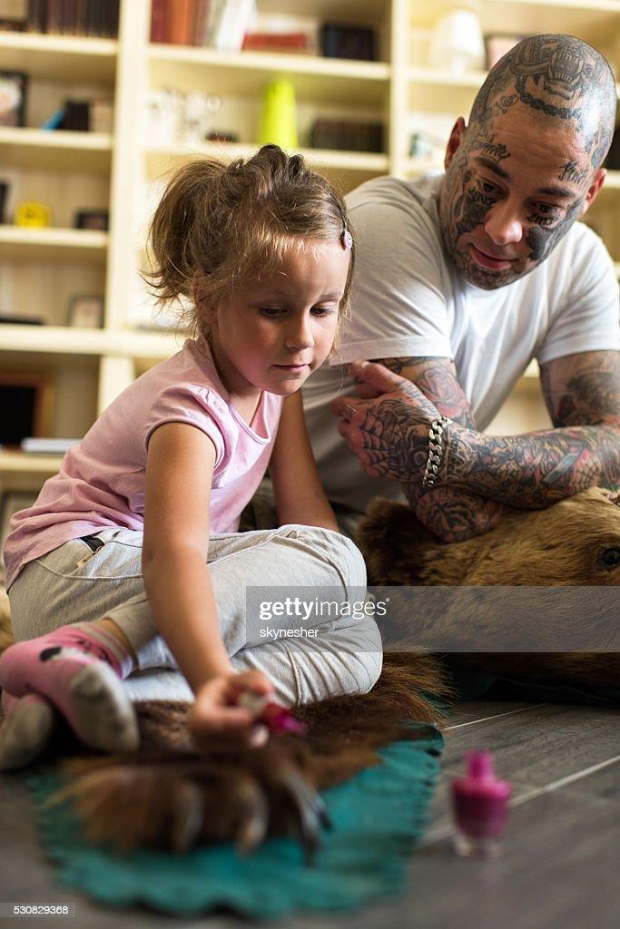 Little girl sitting on bearskin rug and polishing bear's claw. : Stock Photo