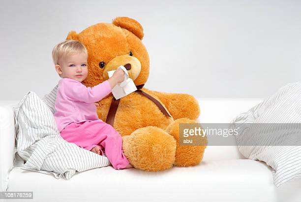 little girl sitting on bed and wiping teddy bear's nose - allegory painting stock pictures, royalty-free photos & images