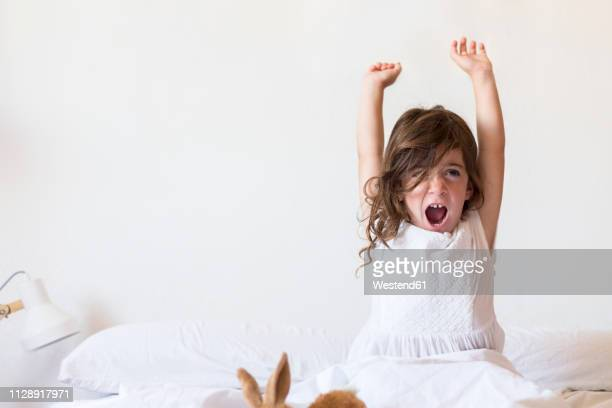 little girl sitting on bed stretching - waking up stock pictures, royalty-free photos & images