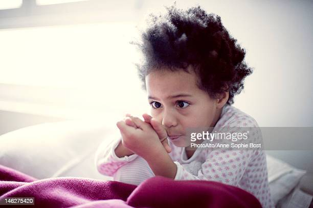 Little girl sitting on bed, studying her hand