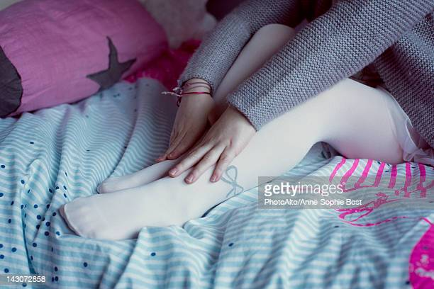 little girl sitting on bed, touching feet, low section - little girls in tights stock photos and pictures