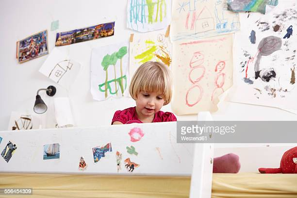 Little girl sitting on bunk bed, playing