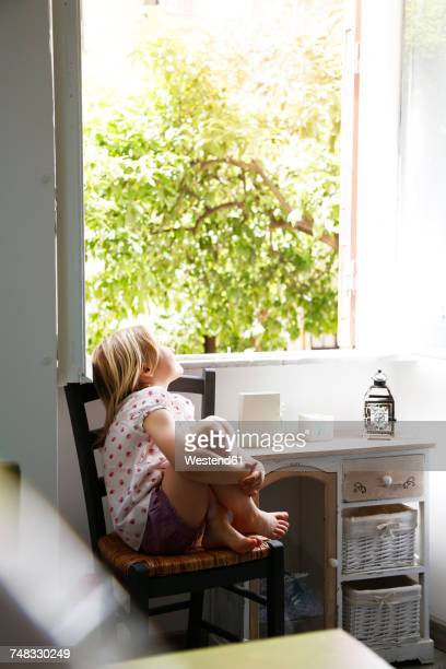 little girl sitting on chair looking out of window - girls open legs stock photos and pictures