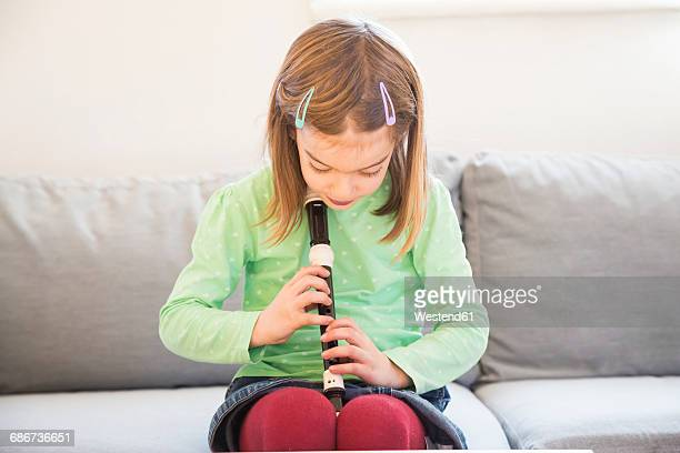 little girl sitting on couch with recorder - recorder musical instrument stock photos and pictures