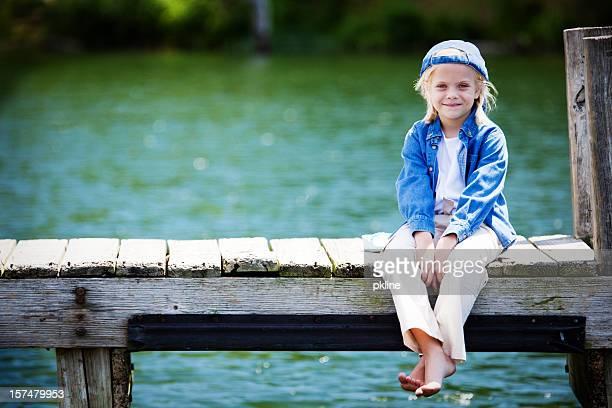 petite fille assise sur un dock - juin photos et images de collection